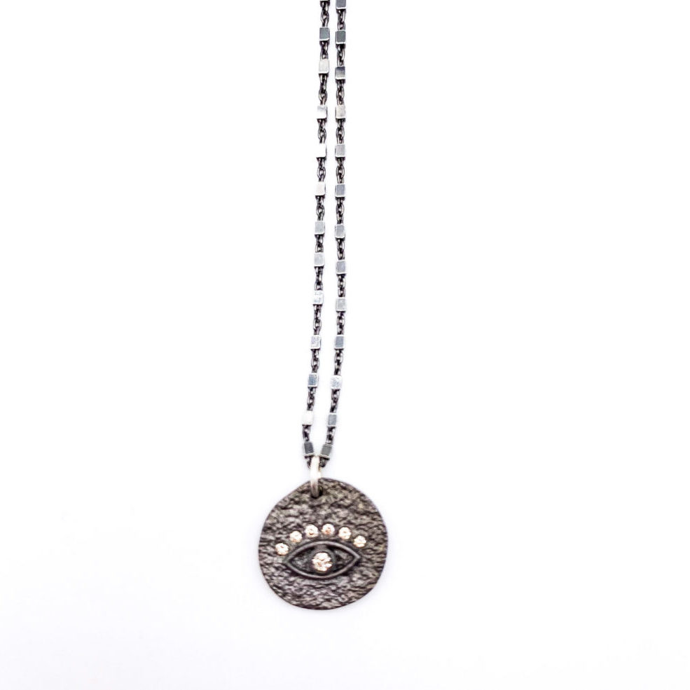 diamond evil eye set on a pounded, darkened sterling silver disc